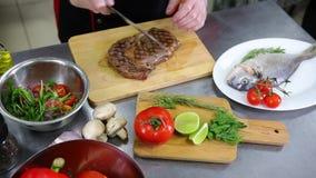 En kock som arbetar i köket En man omkring som klipper köttbiffen lager videofilmer