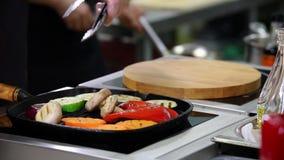 En kock som arbetar i köket En man som upp värmer champinjonerna och grönsakerna i pannan lager videofilmer