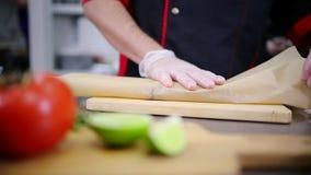 En kock som arbetar i köket Sätta biffen i ett papper arkivfilmer