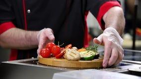 En kock som arbetar i köket Tjänande som stekte grönsaker på ett träskrivbord stock video