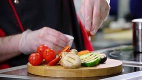 En kock som arbetar i köket Tjänande som stekte grönsaker på skrivbordet stock video