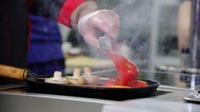 En kock som arbetar i köket Uppvärmning upp champinjonerna och grönsakerna i pannan stock video