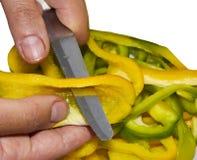 En kock som skivar in i remsor av peppar Royaltyfri Foto