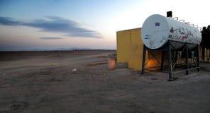En koja och en vattenbehållare i mitt av öknen i Saudiarabien på solnedgången royaltyfri foto