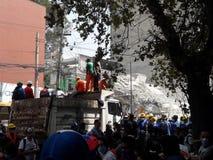 En kollapsad kommersiell mitt bryner nästan i avenidaen Medellin i Mexico - stadsjordskalv Royaltyfri Fotografi