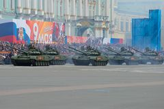 En kolonn av ryssen tankar mot bakgrunden av festliga ställningar En genrep av en ståta i hedern av Victory Day Arkivbild