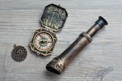 En kompass, en monokel och en piratkopieramedaljong för en piratkopiera spelar arkivbild