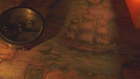 En kompass nära de två tända stearinljusen stock video