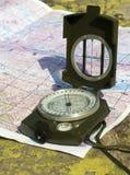 En kompass och en bergöversikt Arkivfoto