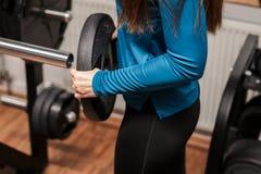 En konditionflicka som staplar lyftande vikt bodybuilding skivstång, idrottshall; royaltyfri illustrationer