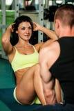 En konditionpargenomkörare - färdiga mann och kvinnan utbildar i idrottshall fotografering för bildbyråer