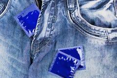 En kondom i blixtlås och två kondomar spridde på jeans Fotografering för Bildbyråer