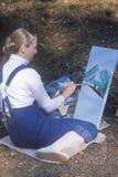 En konstdeltagare som målar ett sceniskt, Fotografering för Bildbyråer