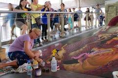 En konstnär (Julie Kirk Purcell) under att dra och att måla hans konstverk 3D. Arkivfoto