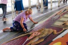 En konstnär (Julie Kirk Purcell) under att dra och att måla hans konstverk 3D. Fotografering för Bildbyråer