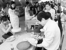 En konstnär målar en framsida av flickan på keramiska produkter Royaltyfri Bild