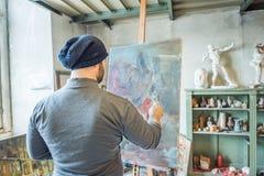 En konstnär som målar ett mästerverk på hans studio royaltyfri foto