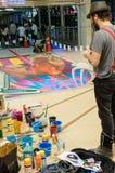 En konstnär (Tony Cuboliquido) under att dra och att måla hans konstverk 3D. Arkivfoto
