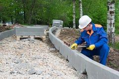 En kontrollarbetare gör en mätning av kvaliteten av kursen för vägkonstruktion arkivbild