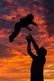 En kontur av en fader som spelar med hans son i inställningssolen Royaltyfria Foton