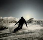 En kontur av en snowboarder som går ner lutningen i det motsättande ljuset Royaltyfria Bilder