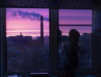 En kontur av ett barnlitet barn på fönstret ser den rosa gryningen och ser rök och stads- hus arkivfoto