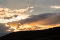 En kontur av ett bergmaximum på solnedgången, under solen rays kommande ut till och med några moln Fotografering för Bildbyråer