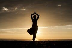 En kontur av kvinnan på en yoga poserar på stranden Royaltyfri Foto