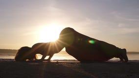 En konturlängd i fot räknat av en kvinna som gör Urdhva Mukha Shvansana på stranden Backbend Sun shines on the background lager videofilmer