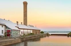 En konverterad fabrik som bygger längs en flodshoreline royaltyfria bilder