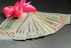 En kopia av pengar i ett rosa band Arkivfoto