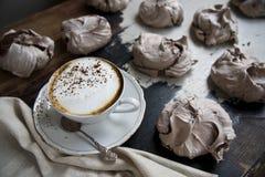En kopp av aromatiskt kaffe med mjölkar och kanel på en lantlig tabell fotografering för bildbyråer