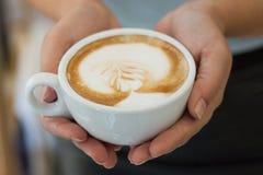 En kopp av cappuccino i de kvinnliga händerna Royaltyfri Bild