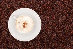En kopp av cappuccino på bakgrund för kaffebönor Royaltyfria Foton