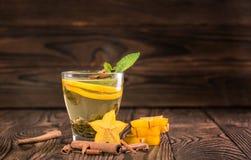 En kopp av citronte med den gröna mintkaramellen på en träsuddig bakgrund Varmt te med carambolaen och kanelbruna pinnar arkivfoton