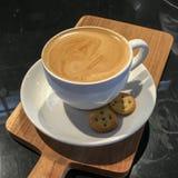 En kopp av den krämiga aromatiska plana serven för vitt kaffe på en träplatta Royaltyfri Foto
