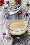 En kopp av den svarta glass bunken för kaffe och med flingor, bär Royaltyfri Fotografi