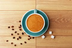 En kopp av doftande kaffe i skum på en trätabell arkivbilder