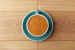 En kopp av doftande kaffe i skum på en trätabell arkivfoto