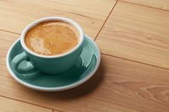 En kopp av doftande kaffe i skum på en trätabell fotografering för bildbyråer