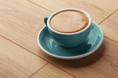 En kopp av doftande kaffe i skum på en trätabell arkivfoton