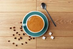 En kopp av doftande kaffe i skum på en trätabell royaltyfria foton