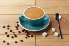En kopp av doftande kaffe i skum på en trätabell arkivbild