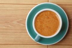 En kopp av doftande kaffe i skum p? en tr?tabell royaltyfri foto
