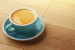 En kopp av doftande kaffe i skum p? en tr?tabell arkivfoto