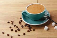 En kopp av doftande kaffe i skum p? en tr?tabell arkivfoton