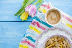 En kopp av doftande kaffe och havregröt med en kvitten Sunda och sunda frukostvårtulpan på en blå träbakgrund Royaltyfri Bild