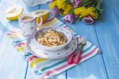 En kopp av doftande kaffe och havregröt med en kvitten Sunda och sunda frukostvårtulpan på en blå träbakgrund Royaltyfri Fotografi