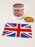 En kopp av engelska te och kexar med en flagga Arkivbild