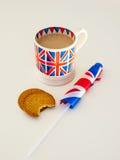 En kopp av engelska te och kexar med en flagga Royaltyfria Bilder